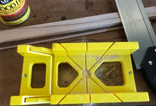 Using the miter box and saw to cut trim